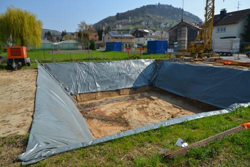 Mit Folie gegen Erosion geschützte Seitenböschungen einer neuen Baugrube